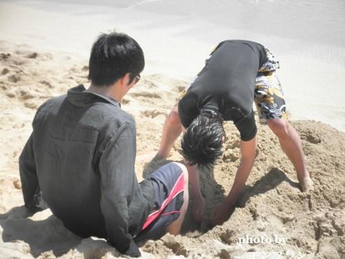 ワイキキビーチで穴を掘って遊ぶ親子